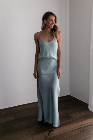 Bridesmaid wearing Grace Loves Lace Belle Silk Split Skirt in Seaglass with pearl earrings
