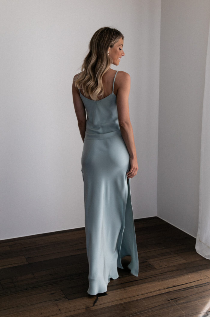 Back shot of bridesmaid wearing Grace Loves Lace Belle Silk Split Skirt in Seaglass with pearl earrings