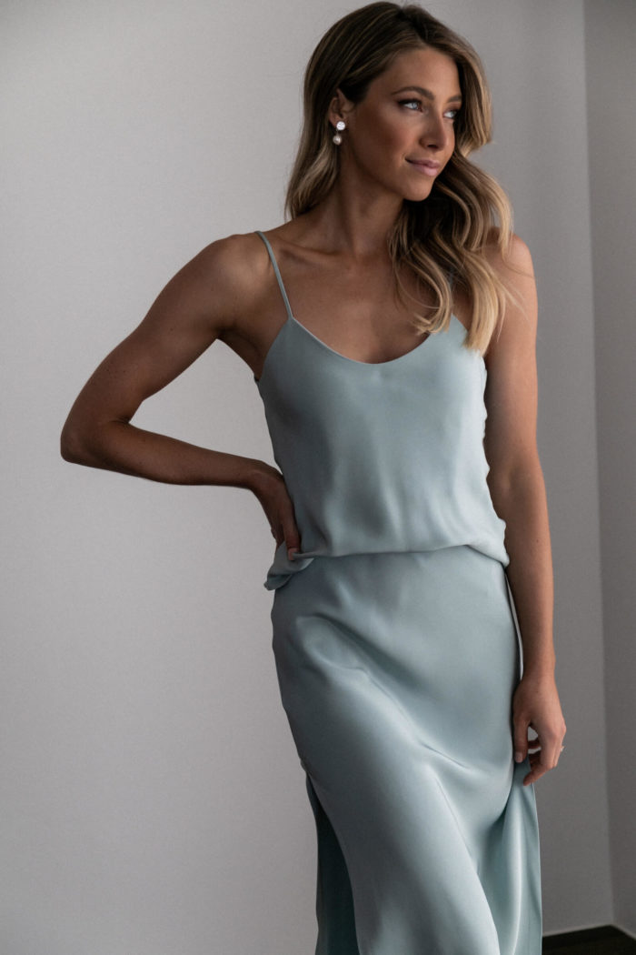 Bridesmaid wearing Grace Loves Lace Belle Long Silk Cami in Seaglass with pearl earrings with hand on hip