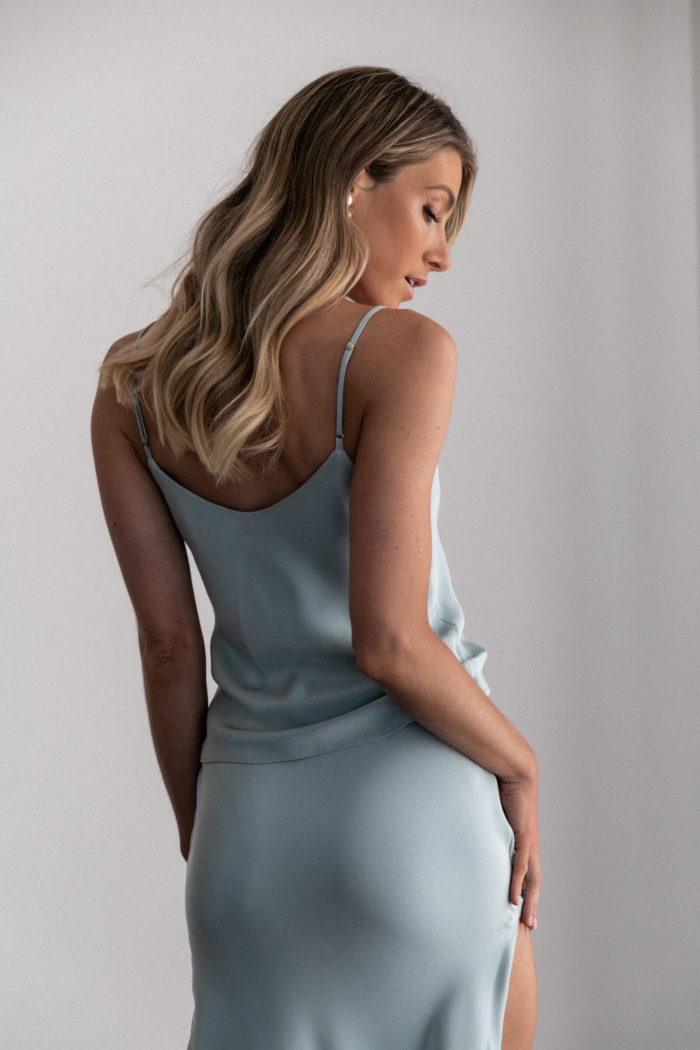 Back shot of bridesmaid wearing Grace Loves Lace Belle Long Silk Cami in Seaglass with pearl earrings