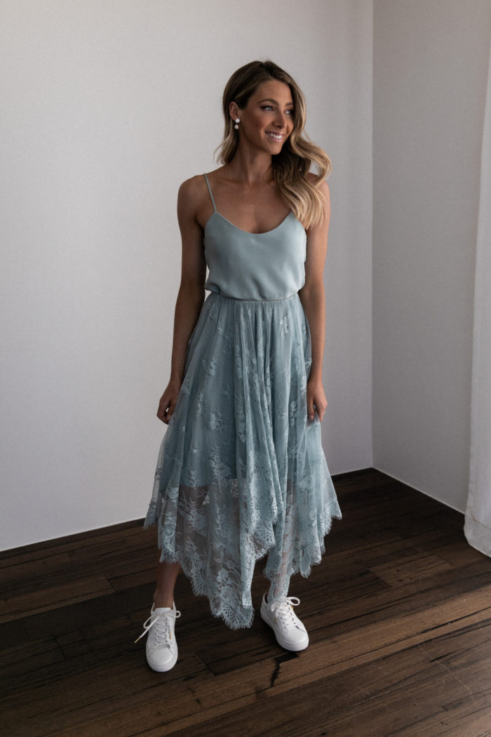 Bridesmaid wearing Grace Loves Lace Belle Lace Swing Skirt in Seaglass with white sneakers