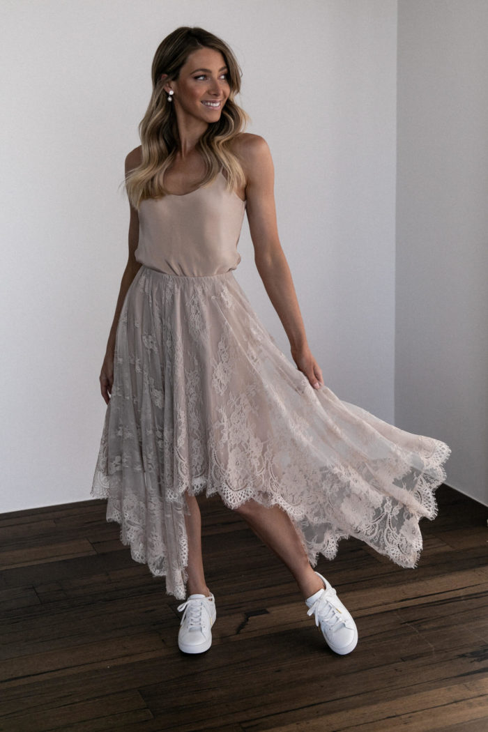 Bridesmaid wearing Grace Loves Lace Belle Lace Swing Skirt in Sandstone with white sneakers