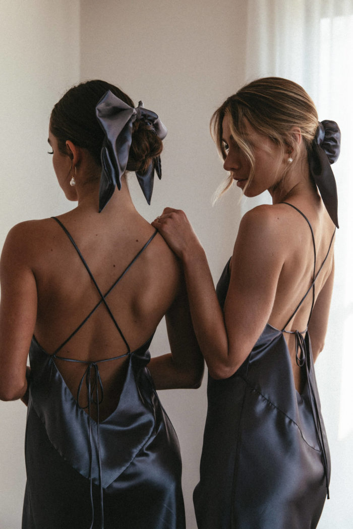 Back shot of bridesmaids wearing Grace Loves Lace Silky Satin Hair Bun and Bow in Steele with simple pearl earrings