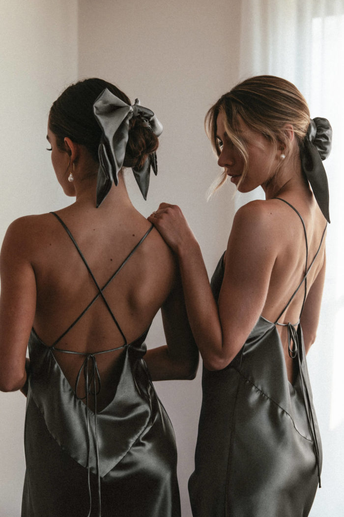 Back shot of bridesmaids wearing Grace Loves Lace Silky Satin Hair Bun and Bow in Olive with simple pearl earrings