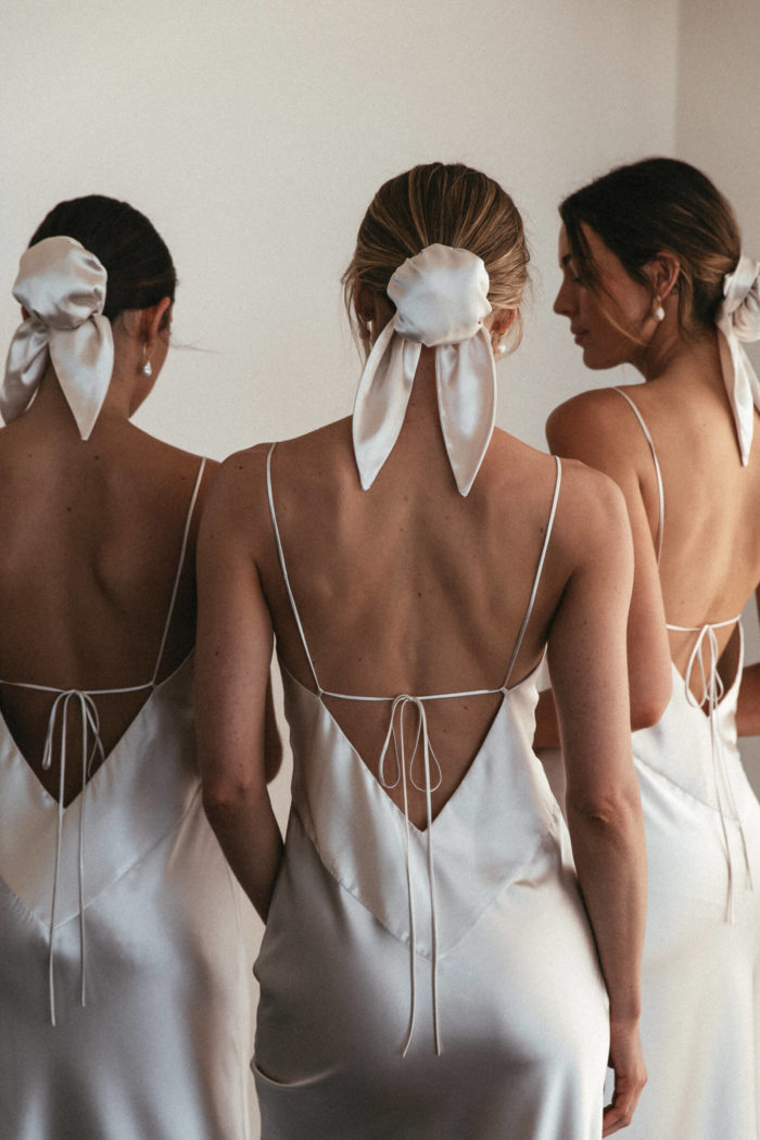 Back shot of bridesmaids wearing Grace Loves Lace Silky Satin Hair Bun in Moonshine with simple pearl earrings