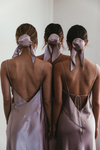Back shot of bridesmaids wearing Grace Loves Lace Silky Satin Hair Bun in Dusk with simple pearl earrings
