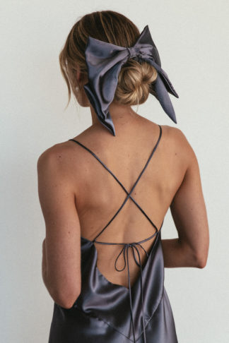 Back shot of bridesmaid wearing Grace Loves Lace Silky Satin Hair Bow in Steele with simple pearl earrings