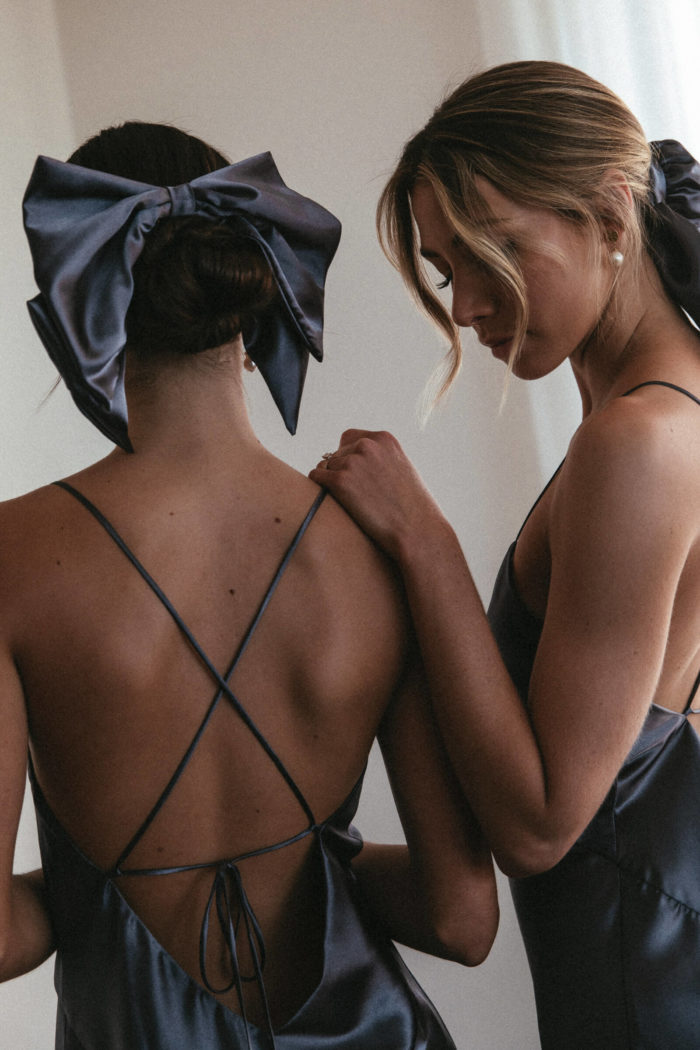 Back shot of bridesmaids wearing Grace Loves Lace Silky Satin Hair Bow and Bun in Steele with simple pearl earrings
