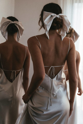 Back shot of bridesmaids wearing Grace Loves Lace Silky Satin Hair Bow in Moonshine