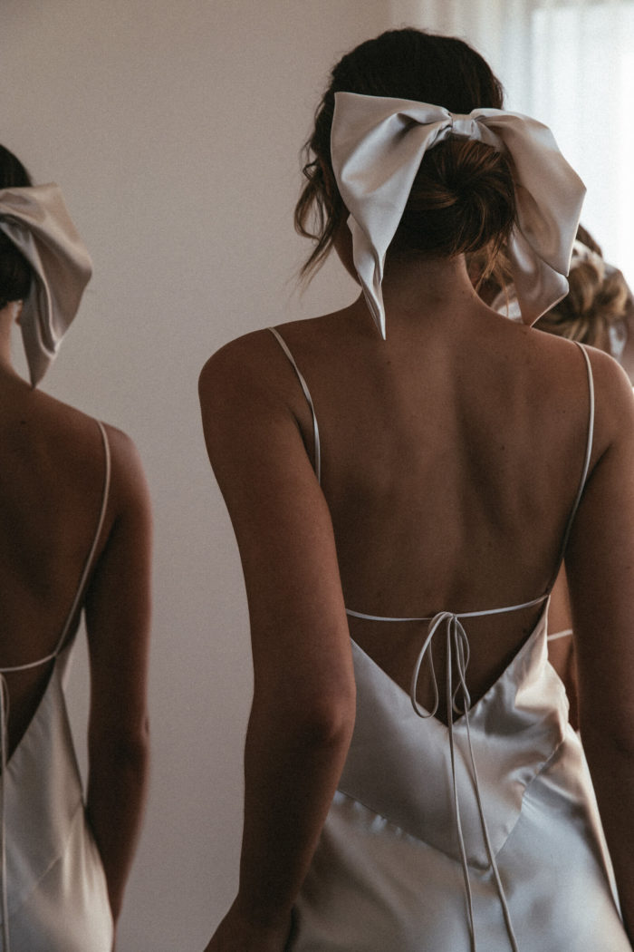 Back shot of bridesmaids wearing Grace Loves Lace Silky Satin Hair Bow in Moonshine with simple pearl earrings
