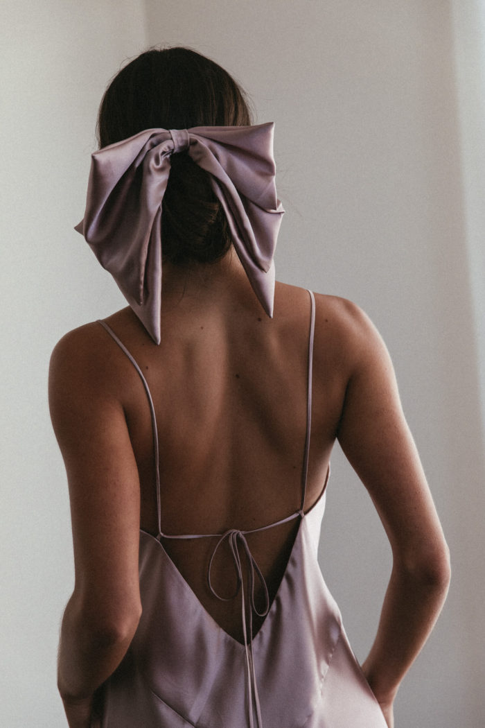 Back shot of bridesmaid wearing Grace Loves Lace Silky Satin Hair Bow in Dusk