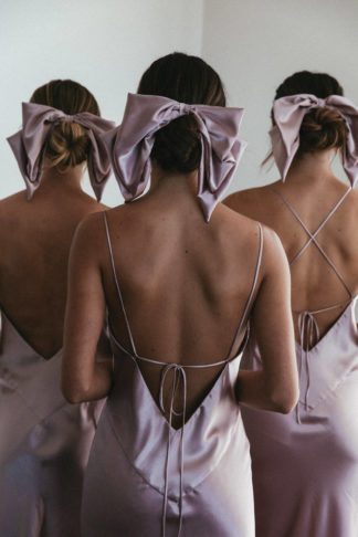 Back shot of bridesmaids wearing Grace Loves Lace Silky Satin Hair Bow in Dusk