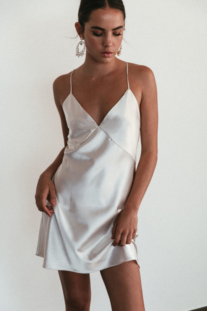 Bridesmaid wearing Grace Loves Lace Silky Satin Mini in Moonshine holding skirt in hand