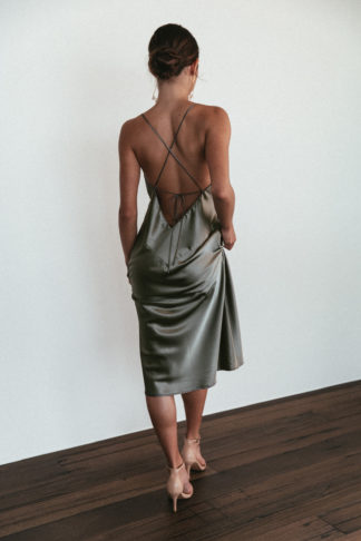 Back shot of brunette bridesmaid wearing Grace Loves Lace Silky Satin Midi in Olive and statement earrings