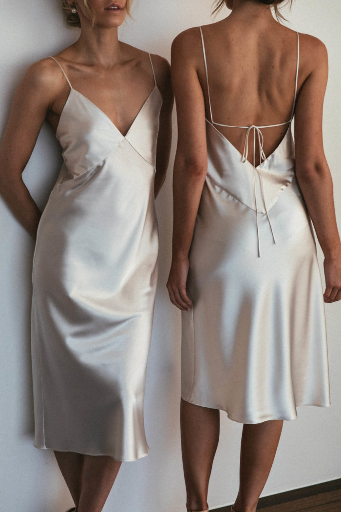 Two bridesmaids wearing Grace Loves Lace Silky Satin Midi in Moonshine leaning against wall