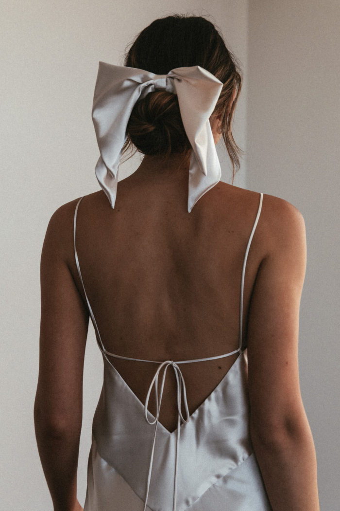 Back shot of bridesmaid wearing Grace Loves Lace Silky Satin Midi in Moonshine and hair bow