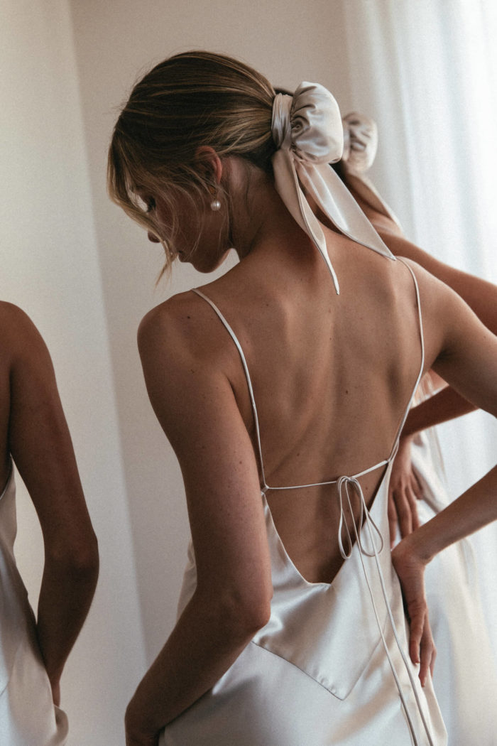Back shot of bridesmaids wearing Grace Loves Lace Silky Satin Midi in Moonshine and hair buns