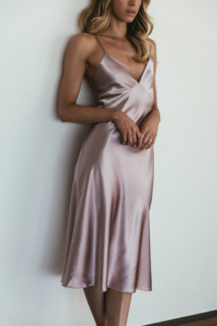 Bridesmaid wearing Grace Loves Lace Silky Satin Midi in Dusk leaning against wall