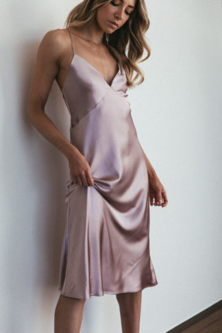 Bridesmaid wearing Grace Loves Lace Silky Satin Midi in Dusk holding skirt in hand