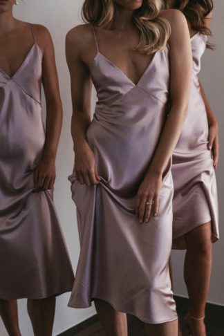 Three bridesmaid wearing Grace Loves Lace Silky Satin Midi in Dusk holding skirt in hand