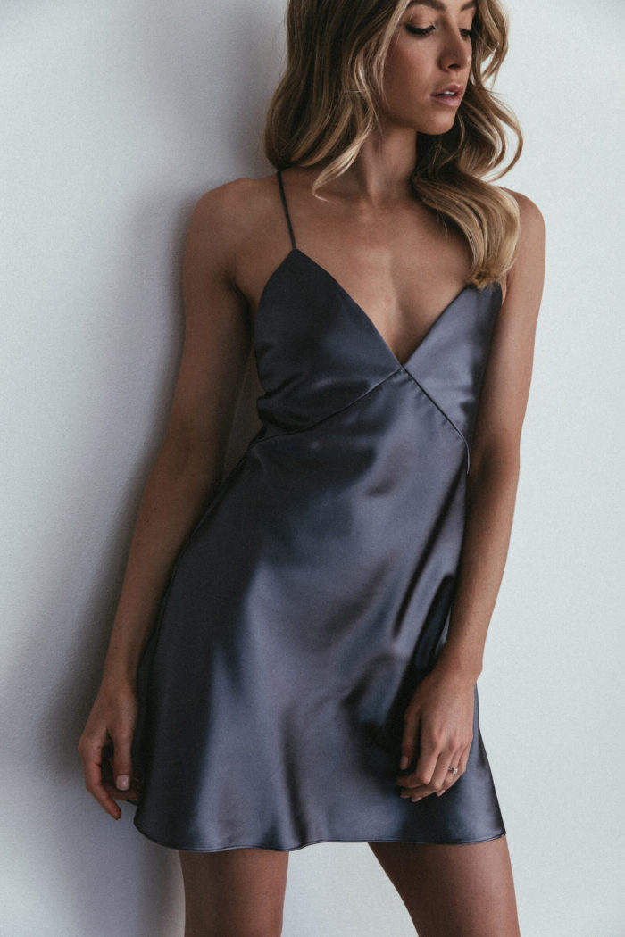 Bridesmaid wearing Grace Loves Lace Silky Satin Mini in Steele leaning against wall