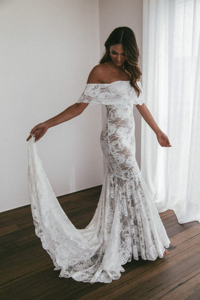 Brunette bride wearing Grace Loves Lace Peaches Gown holding skirt with finger loop