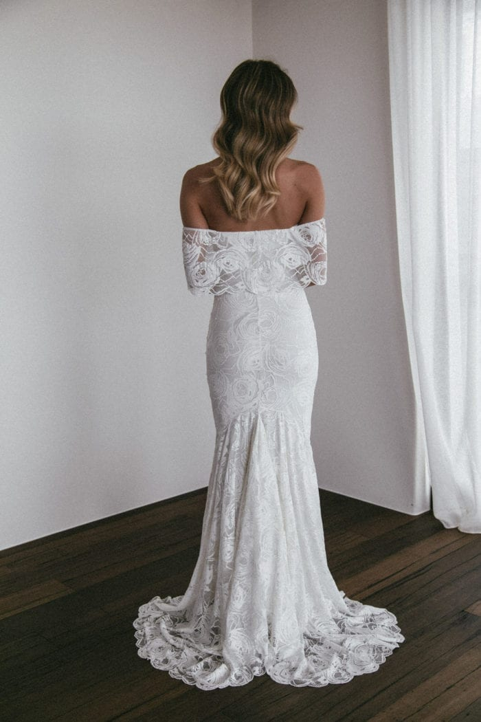 Back shot of brunette bride wearing Grace Loves Lace Peaches Gown holding skirt in hand