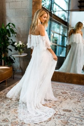 Back shot of blonde bride wearing Grace Loves Lace Florence Gown in Ivory looking at floor in front of mirror