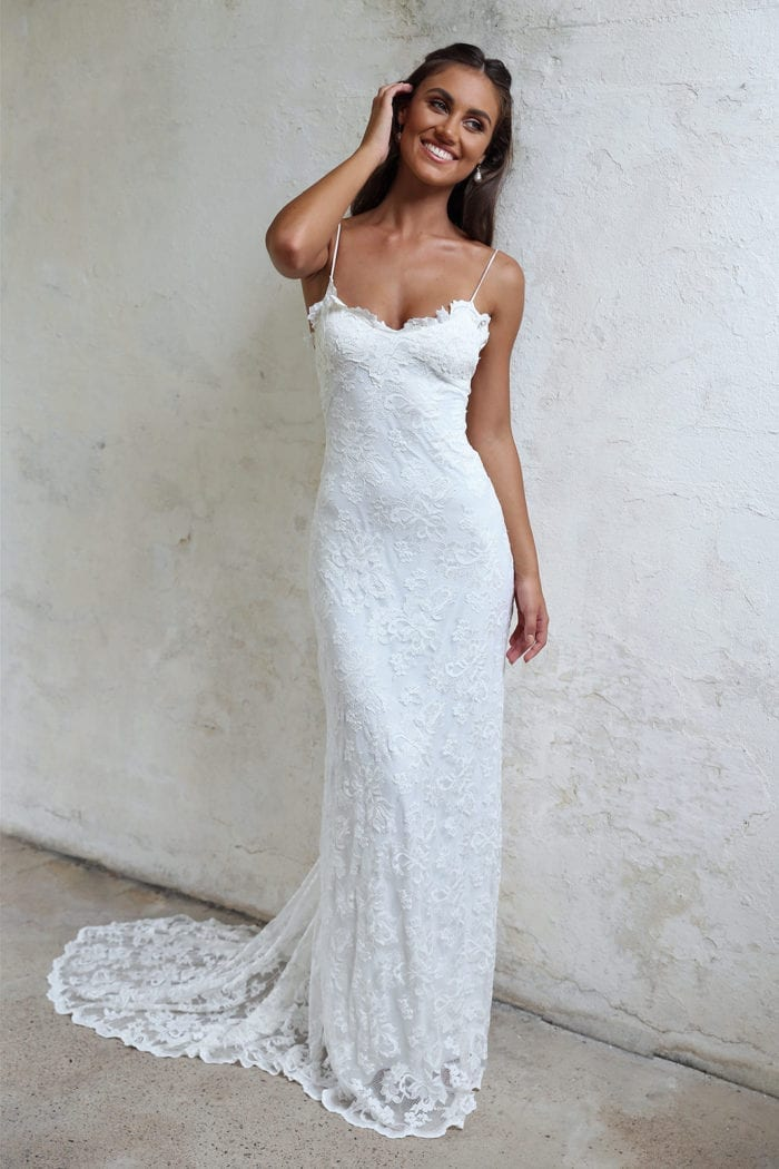 Brunette bride wearing Grace Loves Lace Mia Gown leaning against wall