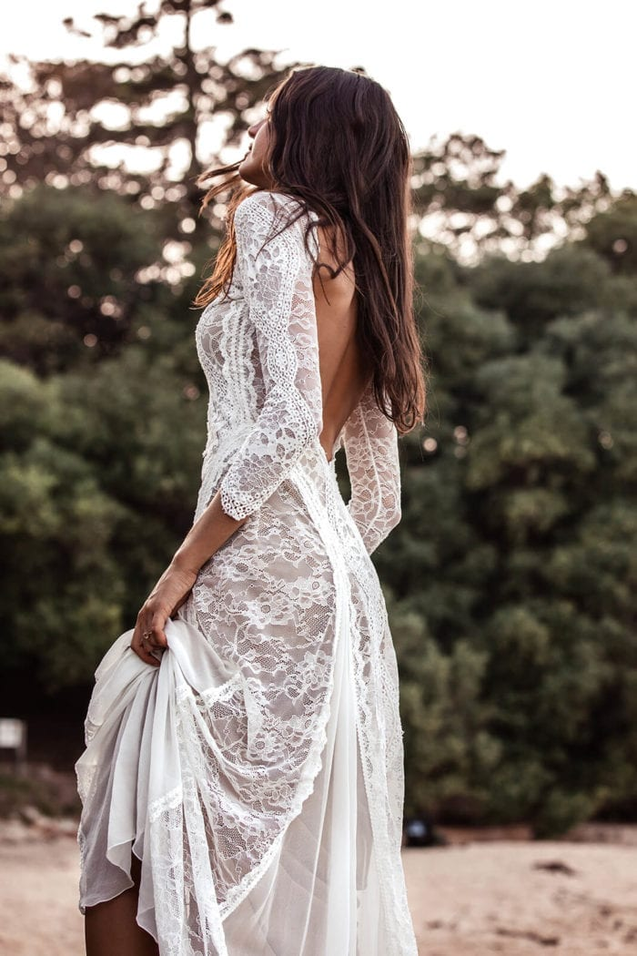 Back shot of bride wearing Grace Loves Lace Inca Gown on beach