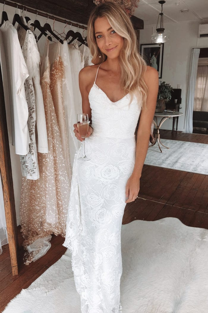 Blonde bride wearing Grace Loves Lace Honey Rose Gown holding champagne glass