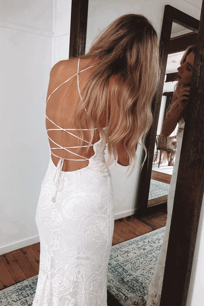 Back shot of blonde bride wearing Grace Loves Lace Honey Rose Gown putting earrings on in mirror