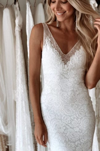 Blonde bride wearing Grace Loves Lace Gia Gown with hand on hair