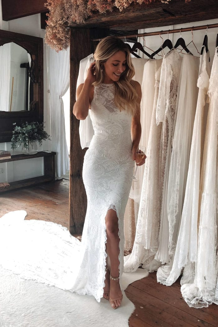 Bride wearing Grace Loves Lace Alexandra Rose Gown with hand on hair holding champagne glass