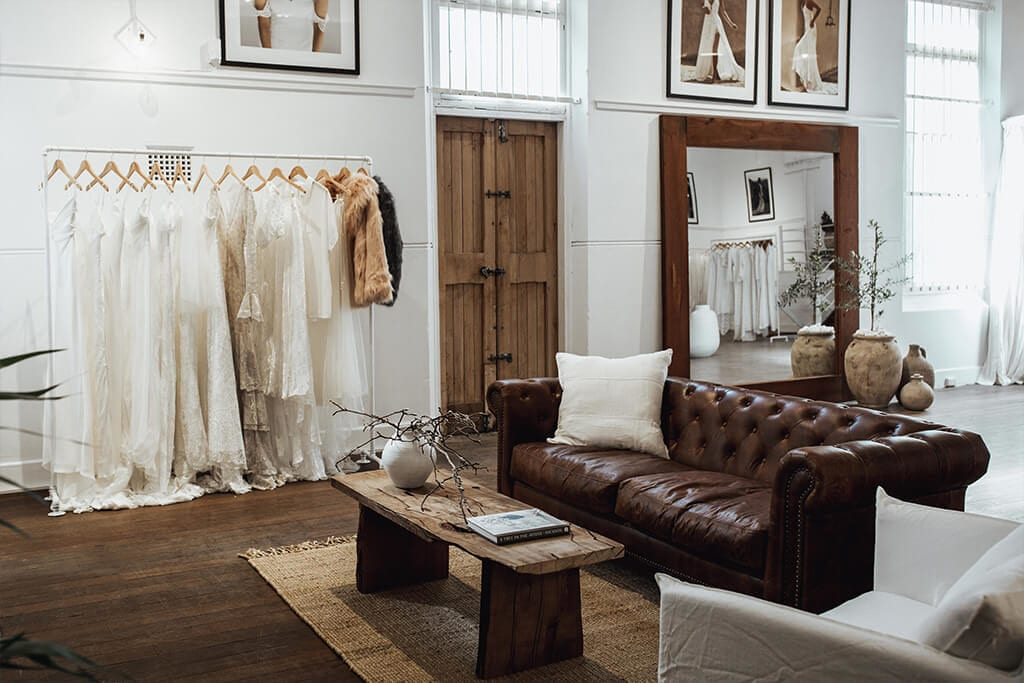 Showroom view of brown leather lounge and coffee table with gowns hanging on a rack in our Perth Bridal Gown Showroom