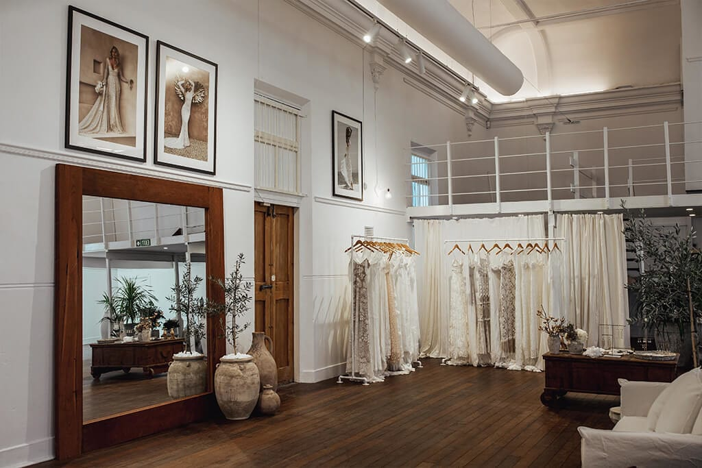 Wide showroom view featuring large mirror with two racks of bridal gowns for fitting in our Perth Bridal Gown Showroom