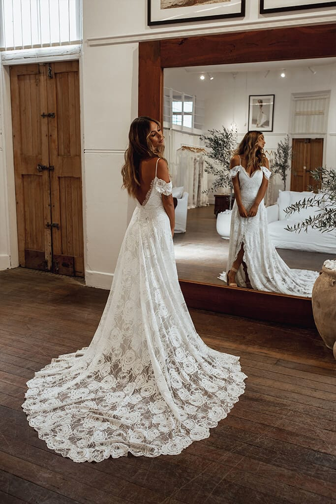 Bride wearing lace gown viewing in mirror