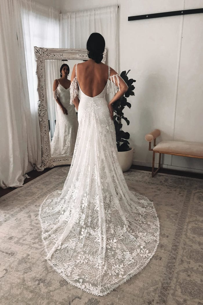 Back shot of bride wearing Grace Loves Lace Sol Gown with hand on hip in front of mirror