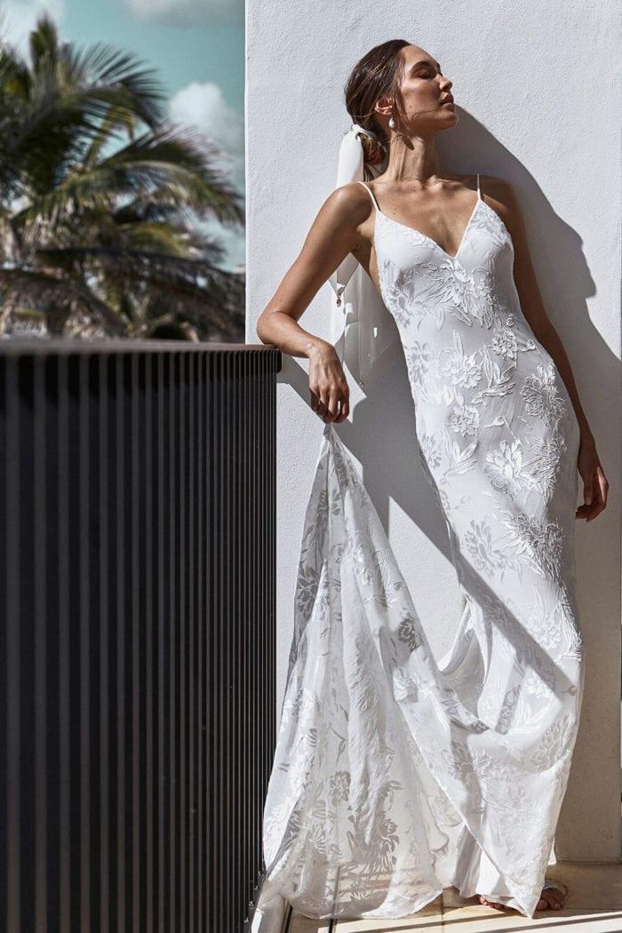 Brunette bride wearing Grace Loves Lace Loyola Gown leaning against rail