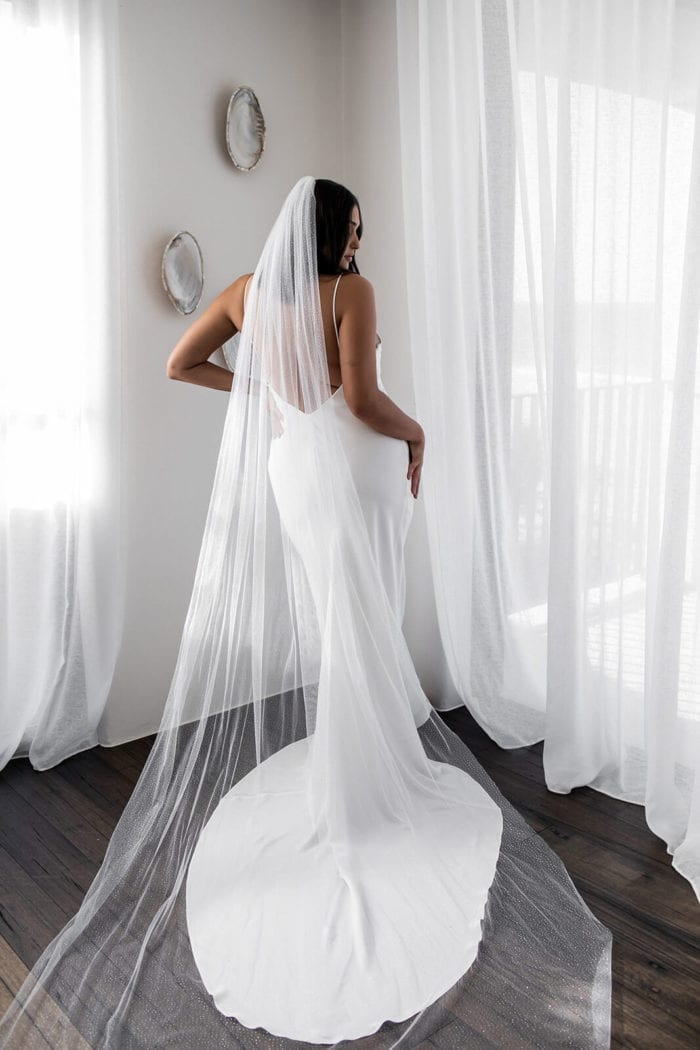 Back shot of bride wearing Grace Loves Lace Summer Gown with veil draped over train