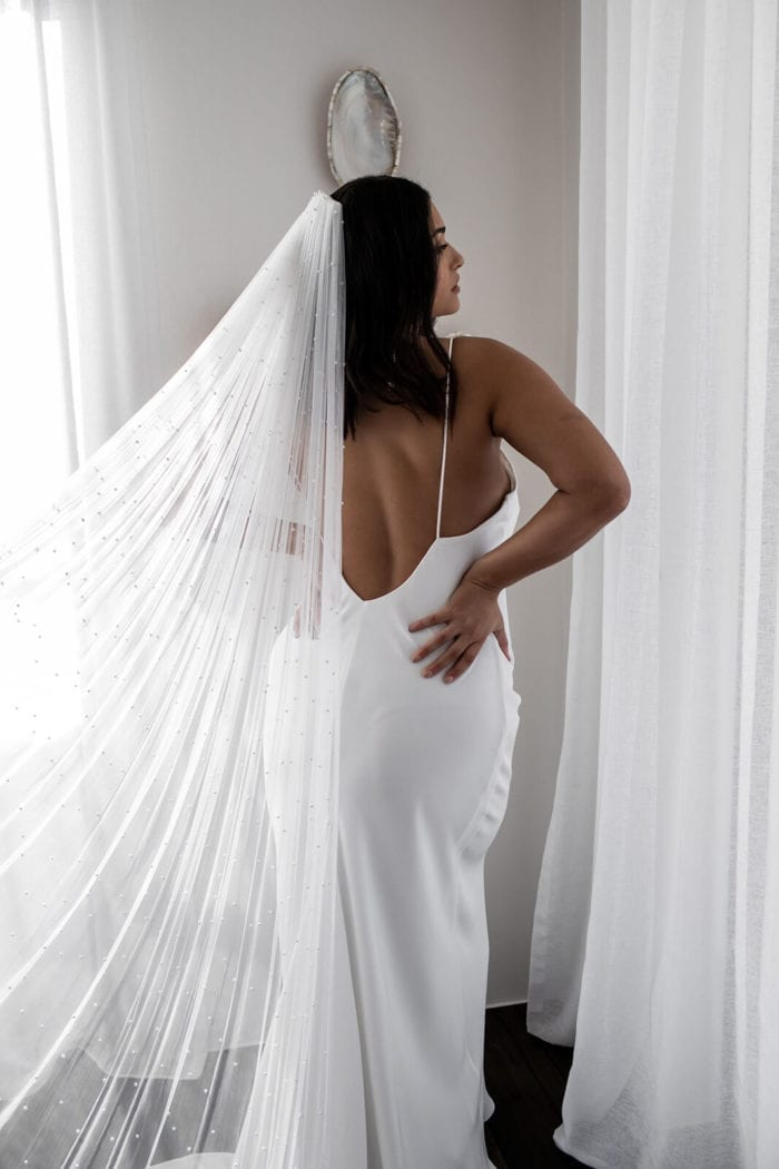 Back shot of bride wearing Grace Loves Lace Summer Gown with hands on hips