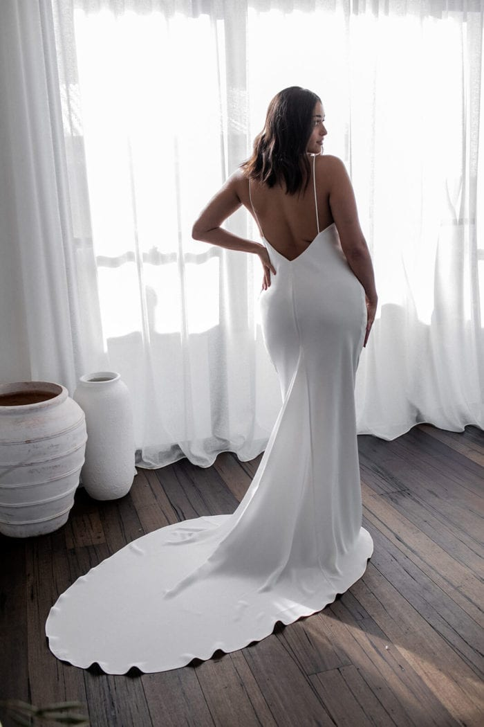 Back shot of bride wearing Grace Loves Lace Summer Gown with hand on hip