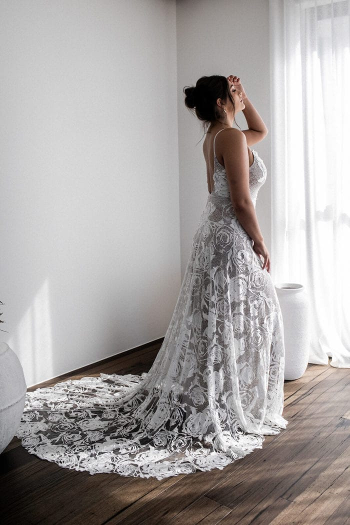 Side shot of bride wearing Grace Loves Lace Rosa Gown with hand on hair