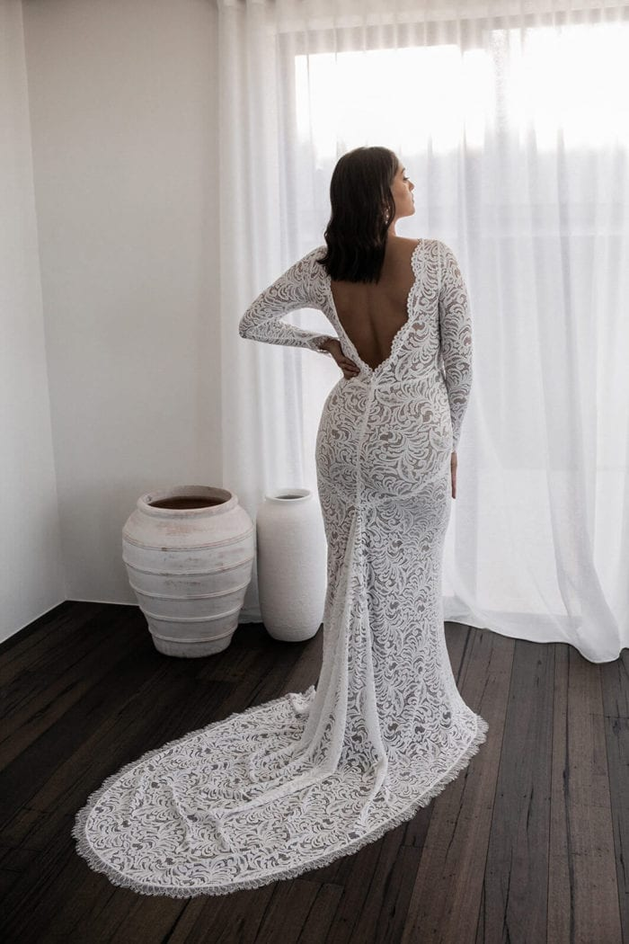 Back shot of bride wearing Grace Loves Lace Orla Gown with hand on hip