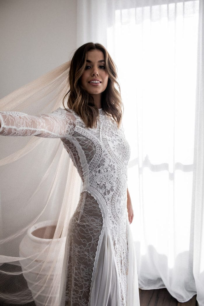 Bride wearing Grace Loves Lace Inca Gown holding veil out in one hand