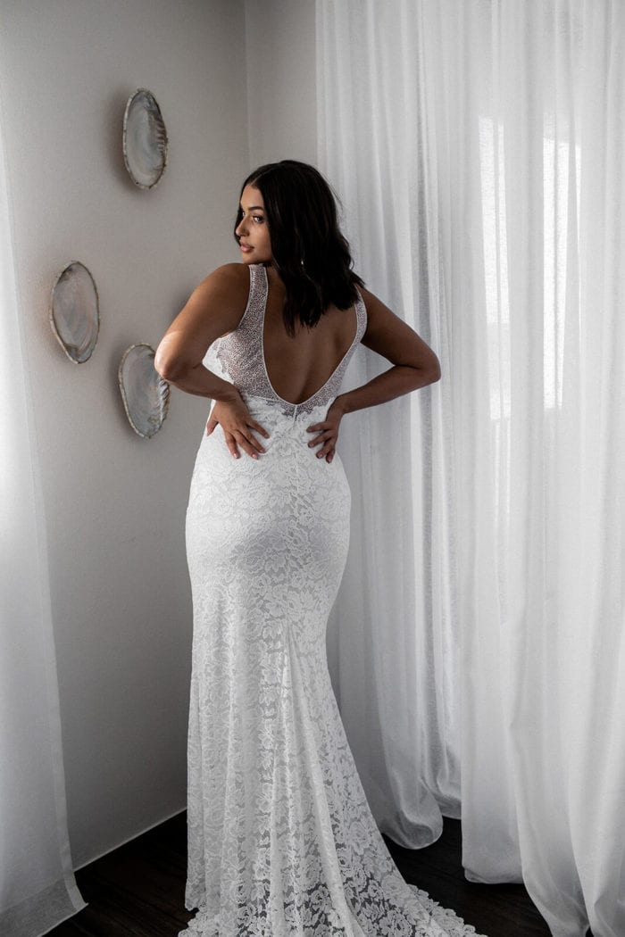 Brunette bride wearing Grace Loves Lace Gia Gown with hands on hips