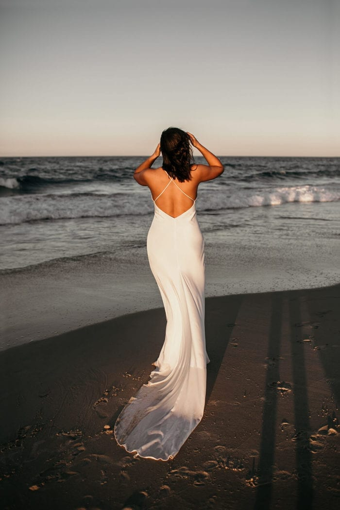 Back shot of brunette bride wearing Grace Loves Lace Dove Gown on beach