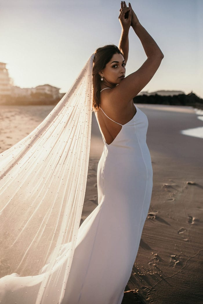 Back shot of brunette bride wearing Grace Loves Lace Dove Gown and veil on beach