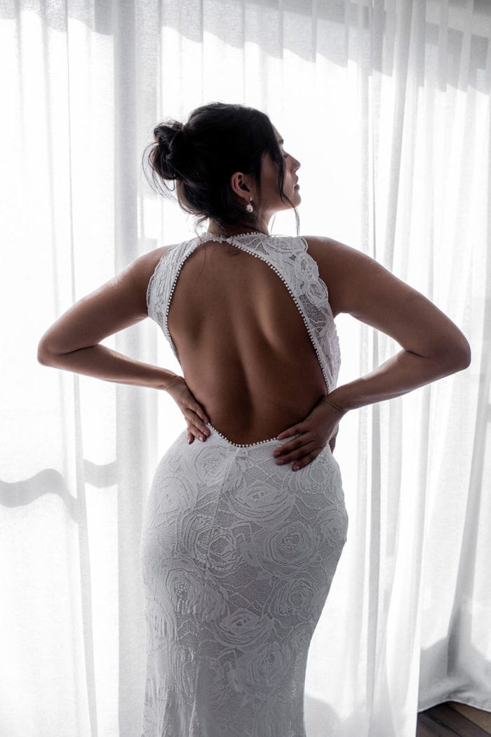 Back shot of bride wearing Grace Loves Lace Alexandra Rose Gown with hands on hips