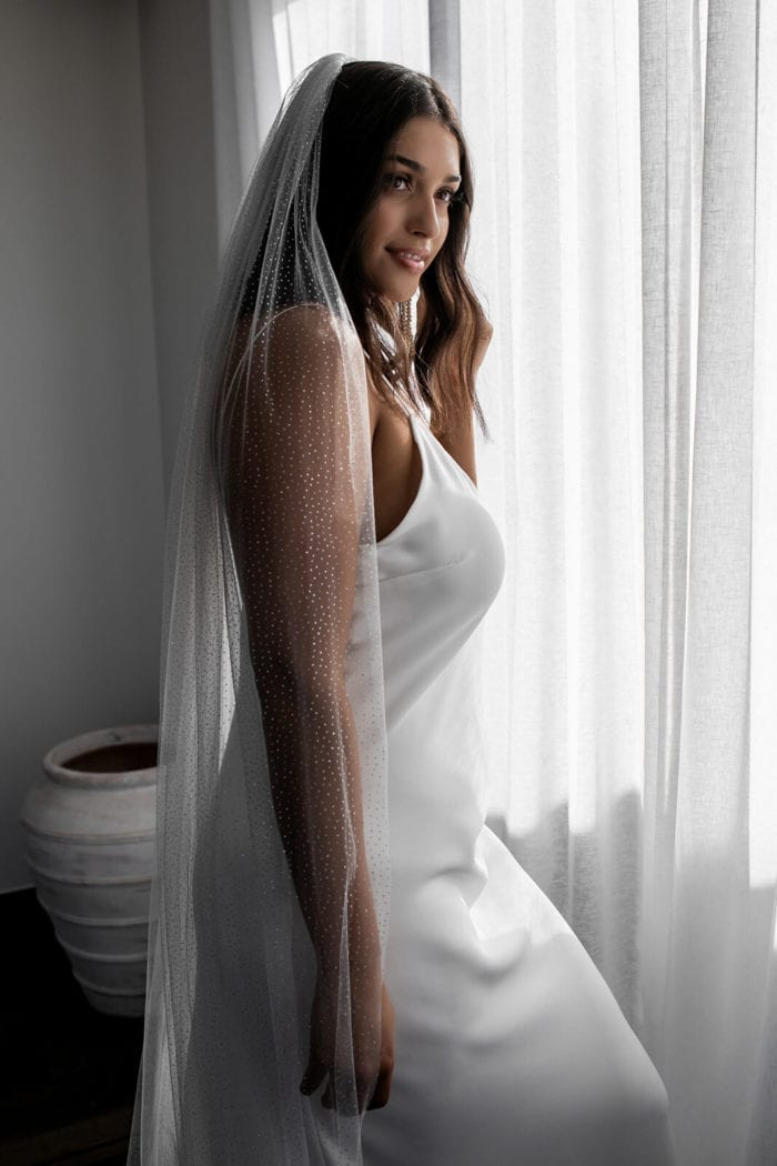 Bride wearing Ivory Silver Grace Loves Lace Shimmy Veil worn by Grace bride standing in front of curtain